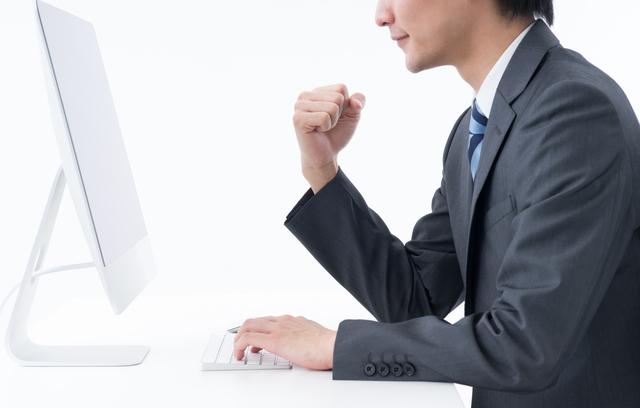 パソコンで審査結果を受け取った男性