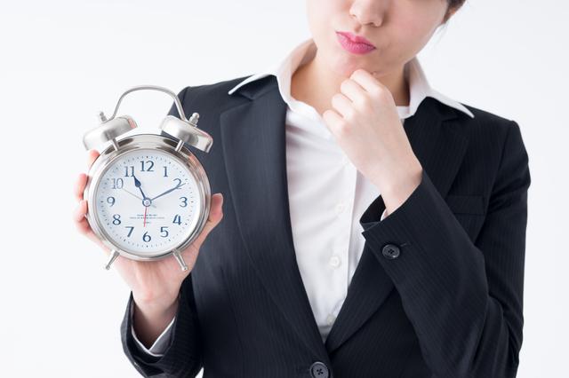 時計を悩ましげに見る女性