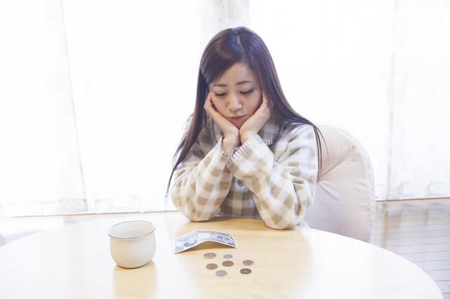 机の上にお金を置いて悩む女性